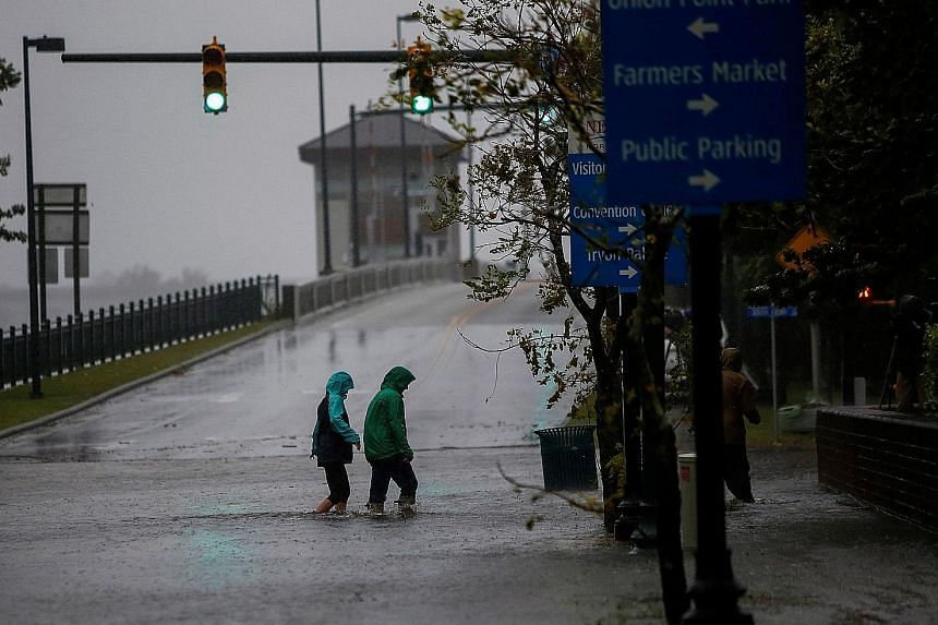 People wading through flood waters in the town of New Bern, in North Carolina, after Hurricane Florence brought strong winds and heavy rain. The hurricane was set to cover nearly all of the state in several metres of water.