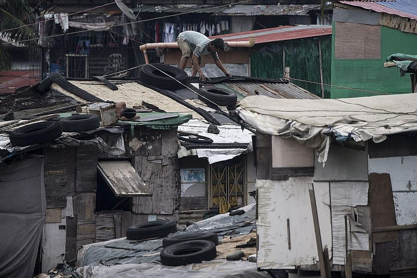 A resident reinforcing the roof of his house with heavy tyres in a Manila slum area yesterday, with Super Typhoon Mangkhut expected to make landfall on northern Luzon early today (Singapore time). Thousands of Filipinos fled their homes and stockpile