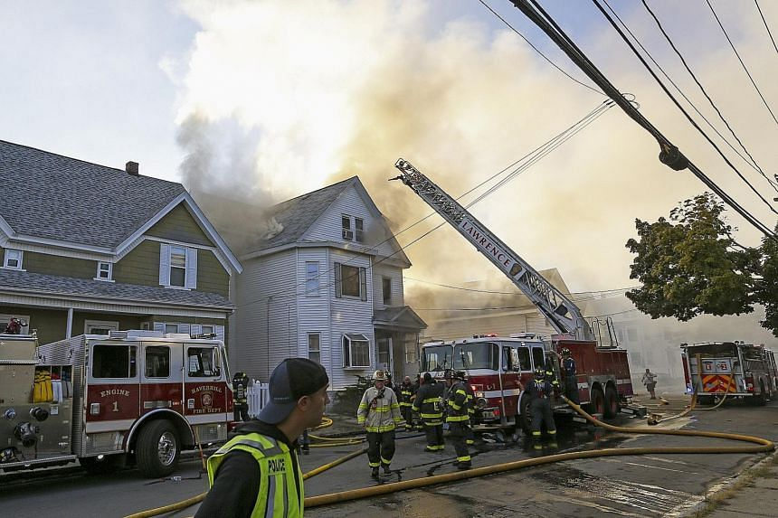 Firefighters battling a blaze at a house in Lawrence, Massachusetts, on Thursday. A series of gas explosions destroyed dozens of homes and other buildings in Andover, North Andover and Lawrence on Thursday - forcing some 8,000 residents to evacuate.