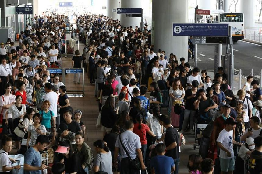 In this photo taken on Sept 5, 2018, passengers stranded overnight at the Kansai International Airport due to Typhoon Jebi queue for buses that will transport them out of the airport in Izumisano city, Osaka prefecture.