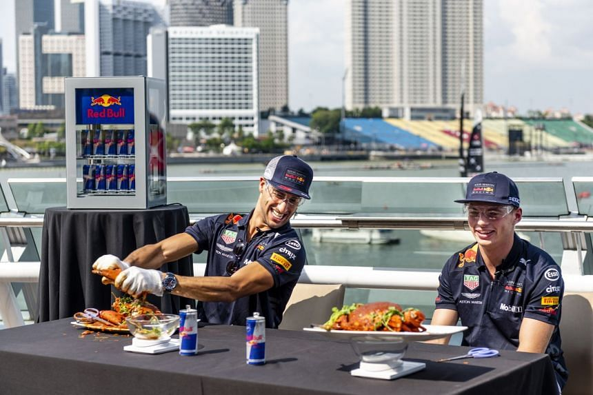 Daniel Ricciardo (from left) and Max Verstappen attempt to de-shell a crab and gather as much meat as possible at a Red Bull event ahead of the Formula One Grand Prix of Singapore, on Sept 13, 2018.