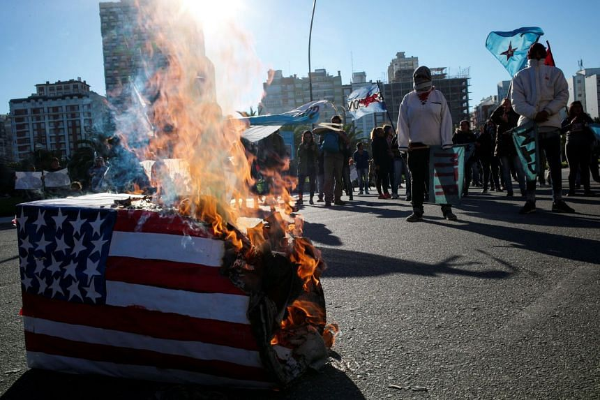 Demonstrators burn a box with the US flag outside the G20 Trade and Investment Ministers Meeting in Mar del Plata, Argentina, on Sept 14, 2018.