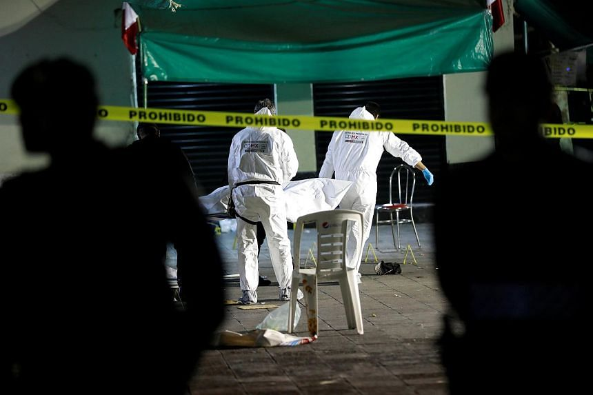 Forensic technicians removing a body from a crime scene where three men were gunned down by unknown assailants at an intersection on the edge of tourist Plaza Garibaldi in Mexico City, on Sept 14, 2018.