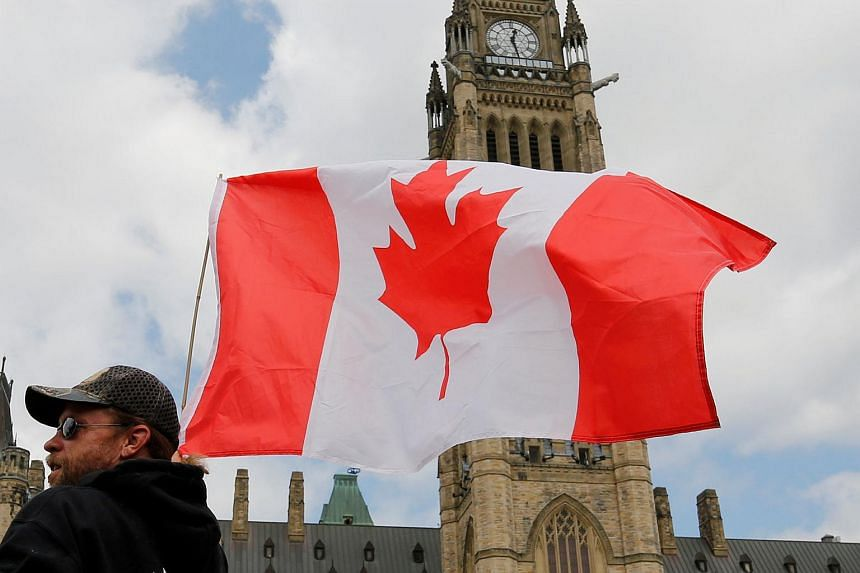 A man holding a Canadian flag during a rally on Parliament Hill in Ottawa, Canada, on July 14, 2018.