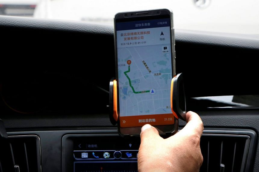 A Didi Chuxing driver checks the information on the app in his car in Beijing, China, on Aug 28, 2018.