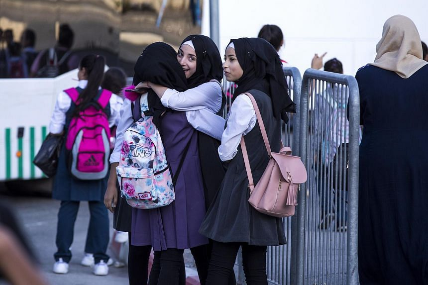 Palestinian school girls embrace as they wait for buses at the Israeli separation barrier inside the Shua'fat Refugee Camp, north of Jerusalem, on Sept 3, 2018.