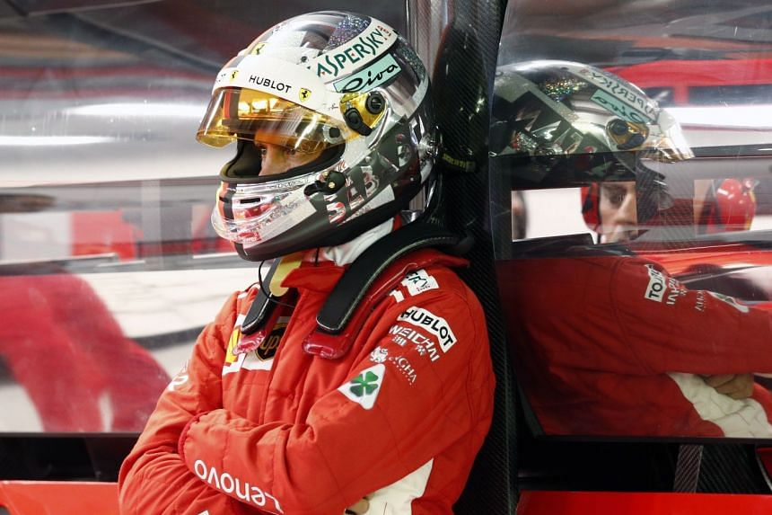 Vettel waits inside the garage during qualifying at the Marina Bay Street Circuit in Singapore.