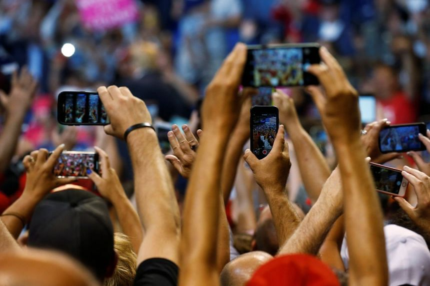Supporters use their cellphones to photograph Donald Trump addressing a campaign rally in August 2018.