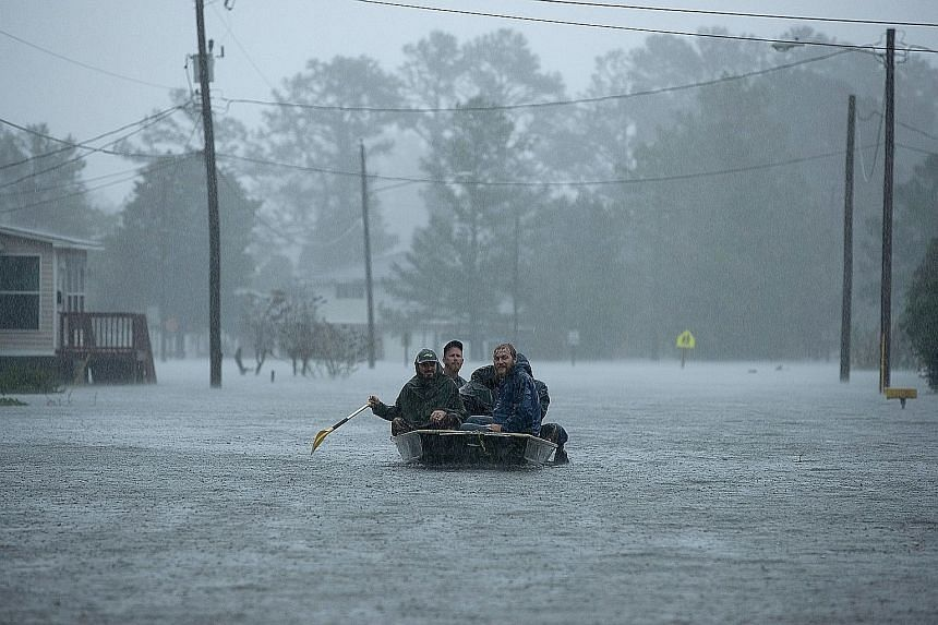 Volunteers rescuing residents from their flooded homes in New Bern, North Carolina, last Friday. The storm surge had overwhelmed the town of 30,000, which is at the confluence of the Neuse and Trent rivers.