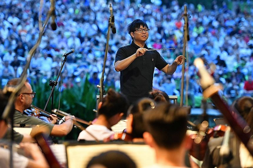 Mr Wong Kah Chun conducting the orchestra in its performance of Beethoven's Symphony No. 7, complete with its rousing finale, to applause from the crowd at the Botanic Gardens yesterday