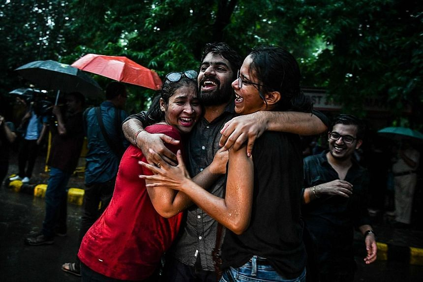 """Couple Sunil Mehra (left) and Navtej Singh Johar felt they were finally """"equal citizens"""". Members and supporters of the LGBT community in New Delhi celebrating the decision to strike down the ban on gay sex."""
