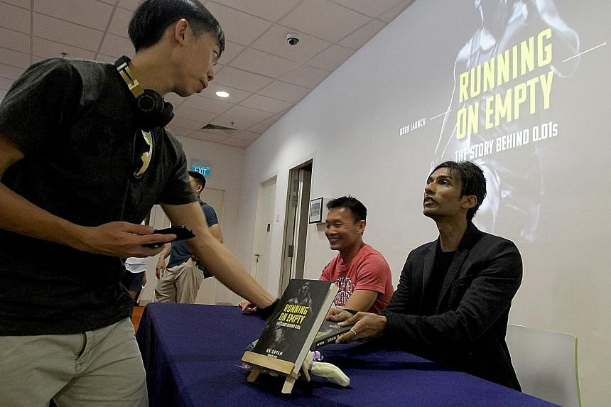 Former national sprinter and current 100m record holder U.K. Shyam (in black blazer) launched his book Running On Empty: The Story Behind 0.01s, written by former runner Kenneth Khoo (in pink), at the Singapore Sports Hub Library yesterday.