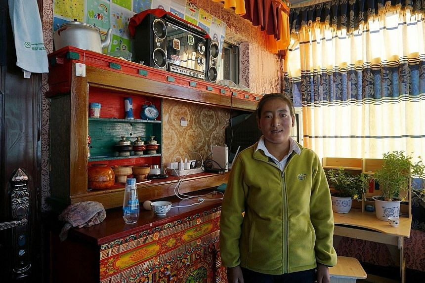 Ms Tseren Yudron in the living room of the family's new home which was provided for free by the government. The family and over 300 other poor households from five villages were moved to the Four Seasons Auspicious Village. Ciwang Nazha, a second-yea