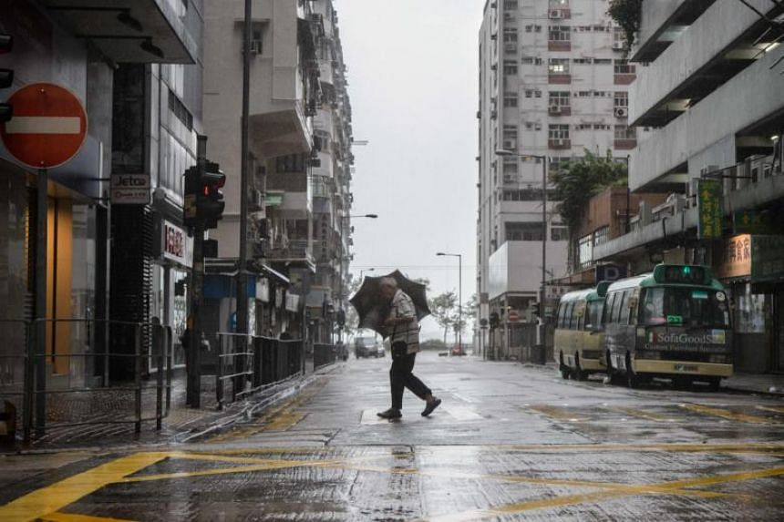 A man uses his umbrella while crossing a road as Super Typhoon Mangkhut edges closer to Hong Kong, on Sept 16, 2018