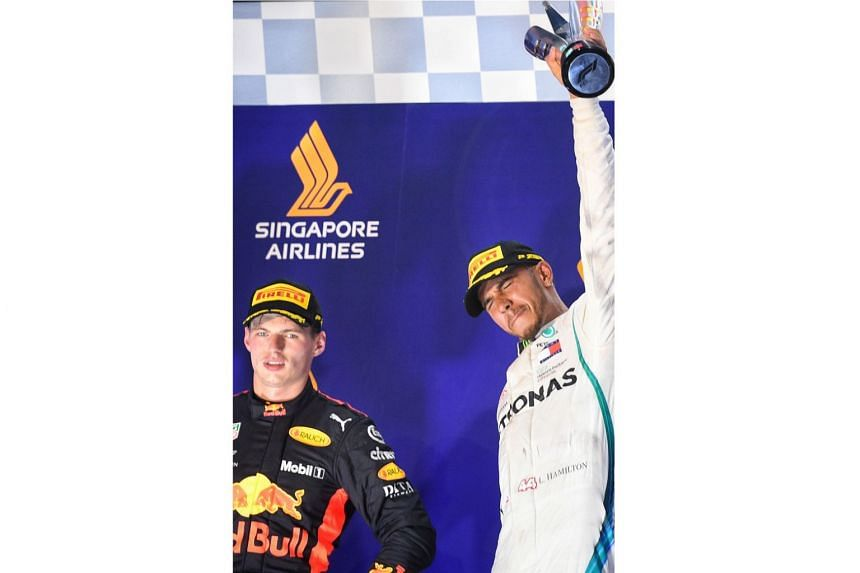 Mercedes' Lewis Hamilton (right) celebrates beside Red Bull's Max Verstappen after winning the 2018 Singapore Airlines Singapore Grand Prix on Sept 16, 2018.