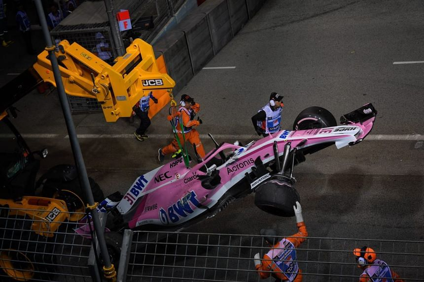 Track marshals removing the car that was driven by Force India's Esteban Ocon after an accident during the 2018 Singapore Airlines Singapore Grand Prix on Sept 16, 2018.