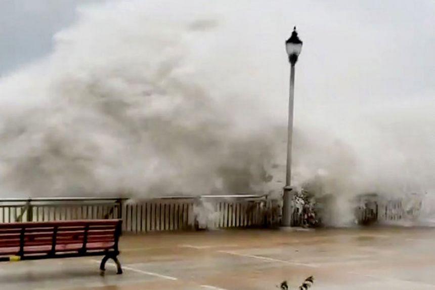 Waves spill over a sea barrier as Typhoon Mangkhut approaches Hong Kong on Sept 16, 2018.