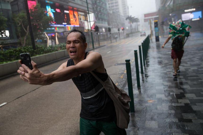 A man takes a video of himself on Nathan Road as Typhoon Mangkhut slams Hong Kong on Sept 16, 2018.