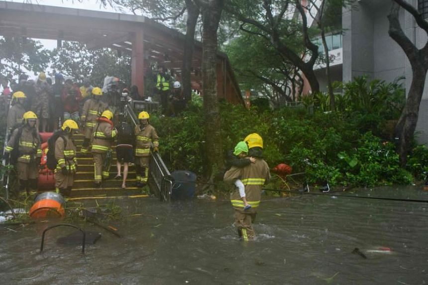 A fire rescue worker helps a child cross a flooded street in the village of Lei Yu Mun during Typhoon Mangkhut in Hong Kong on Sept 16, 2018.