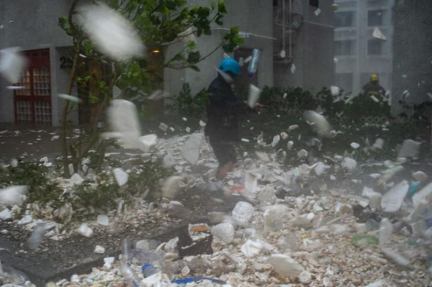 A photojournalist walks amongst plastic debris blown by strong winds during Typhoon Mangkhut in Hong Kong on Sept 16, 2018.