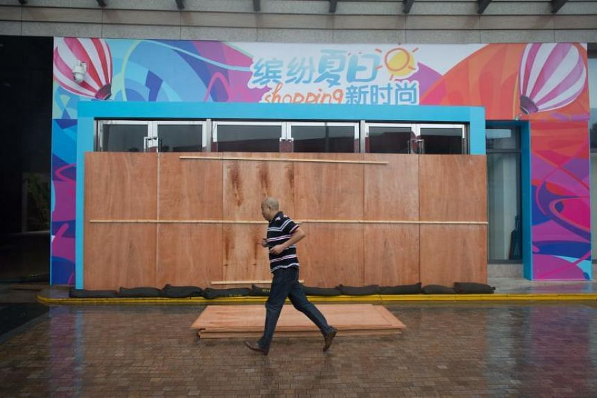 A man runs past a closed shop ahead of the arrival of Typhoon Mangkhut in Yangjiang, China, on Sept 16, 2018.