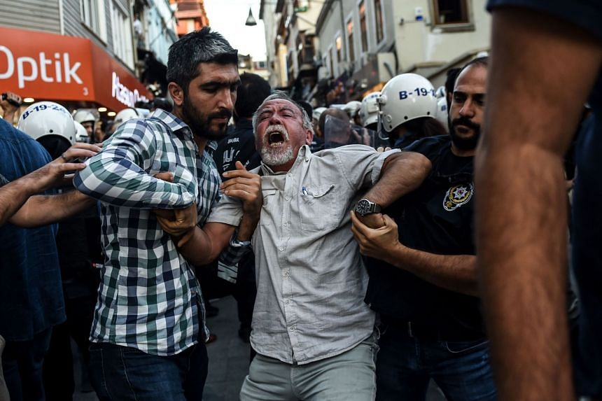 Turkish police officers arrest protesters, gathered in support of workers that were arrested earlier for protesting over labour conditions at Istanbul's new airport, in Istanbul, on Sept 15, 2018.