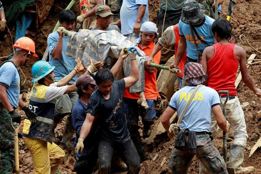 Rescuers carrying a recovered body at a mining camp in Itogon, Bengueta after a landslide was unleashed by super typhoon Mangkhut, on Sept 17, 2018.
