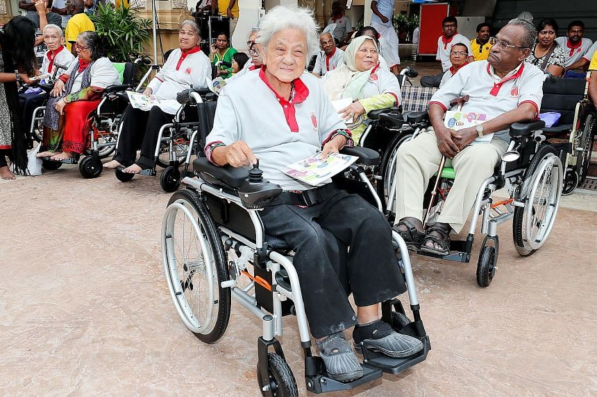 Madam Tan Beng Kee, 76, trying out a motorised wheelchair yesterday. Seven seniors each received a gift of a motorised wheelchair at a charity event, at the Sri Thendayuthapani Temple, organised by the Chettiars' Temple Society. The society also dona