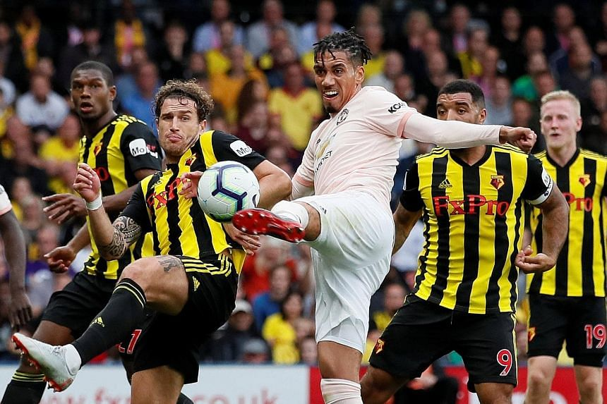 Top Chris Smalling volleying in United's second goal in the Premier League game against the previously unbeaten Watford at Vicarage Road on Saturday. Above Goalkeeper David de Gea saving Christian Kabasele's header in stoppage