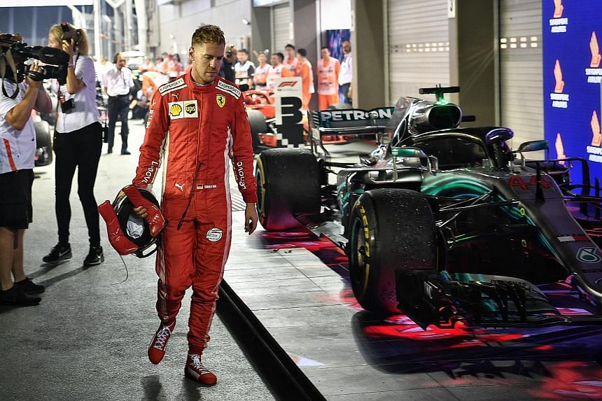 A downcast Sebastian Vettel walking past the Mercedes of Singapore Grand Prix winner Lewis Hamilton, after finishing third in the race to fall further behind the Briton in the drivers' championship. Esteban Ocon's car being removed from the track, af