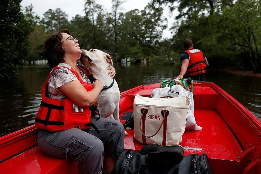 Ms Susan Hedgpeth and her dog Cooper being evacuated to higher ground by the US Coast Guard in Lumberton, North Carolina. Florence has wreaked havoc, knocking out power and devastating communities.