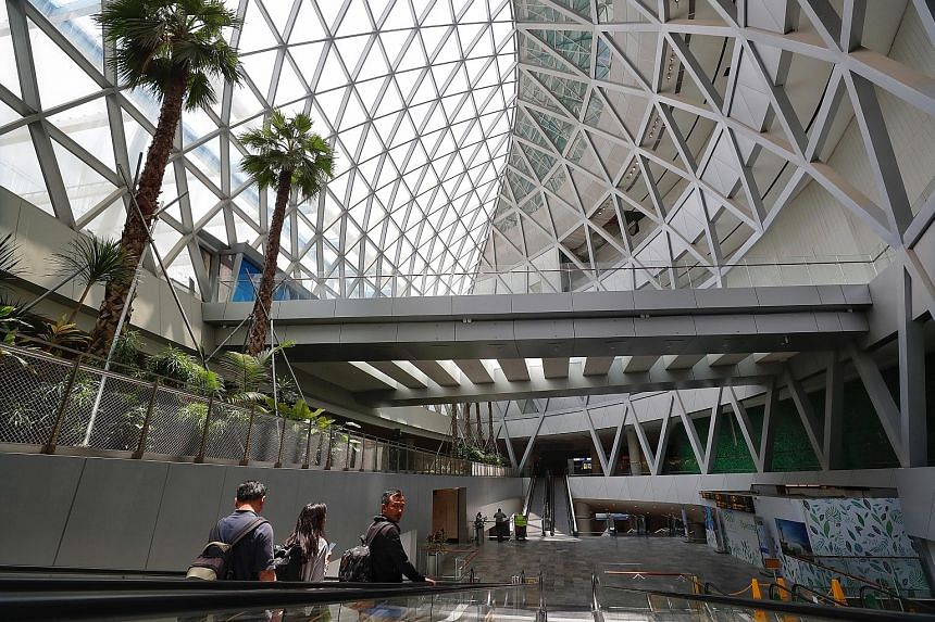 Above: Visitors using a travelator at an open area of Jewel Changi Airport. Left: A skylight architectural feature at the upcoming development, which will also showcase a 40m-high indoor waterfall and a five-storey garden.