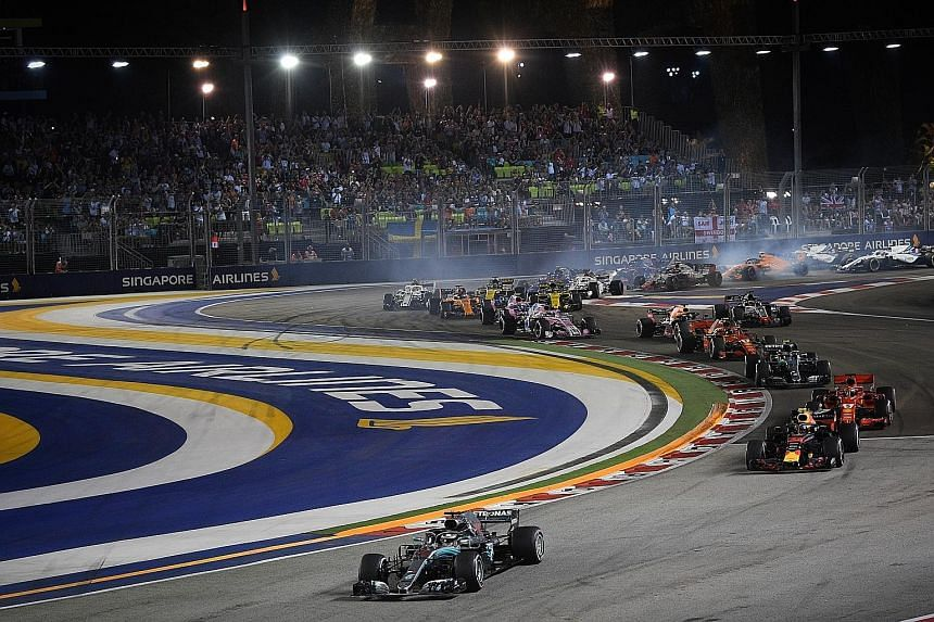 Mercedes driver Lewis Hamilton leading the pack at the Marina Bay Street Circuit last night. Singapore GP attributed this year's jump in attendance to its offerings, such as family-friendly initiatives and strong entertainment acts.