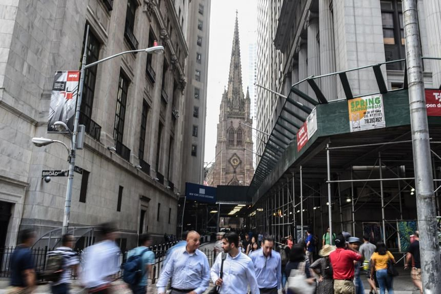 People exit the New York Stock Exchange building along Wall Street, on Aug 1, 2018.