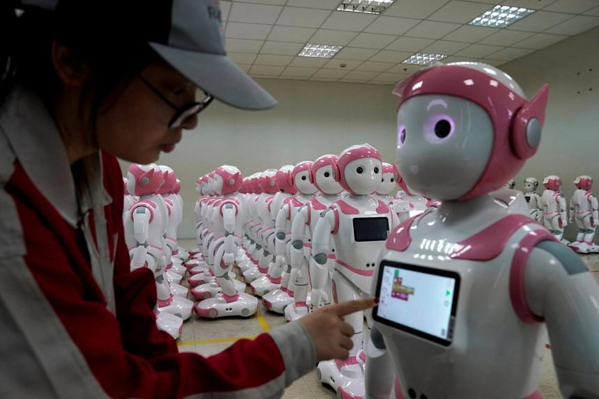A worker puts finishing touches to an iPal social robot, designed by AvatarMind, at an assembly plant in Suzhou, Jiangsu province, China, on July 4, 2018.