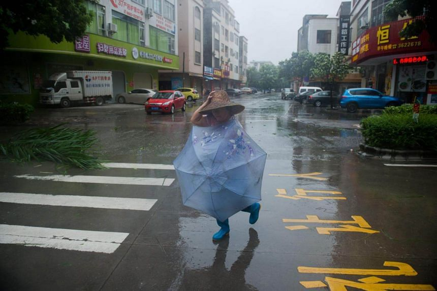 A woman crosses a street during strong winds and rain ahead of the arrival of Super Typhoon Mangkhut in Yangjiang, on Sept 16, 2018.