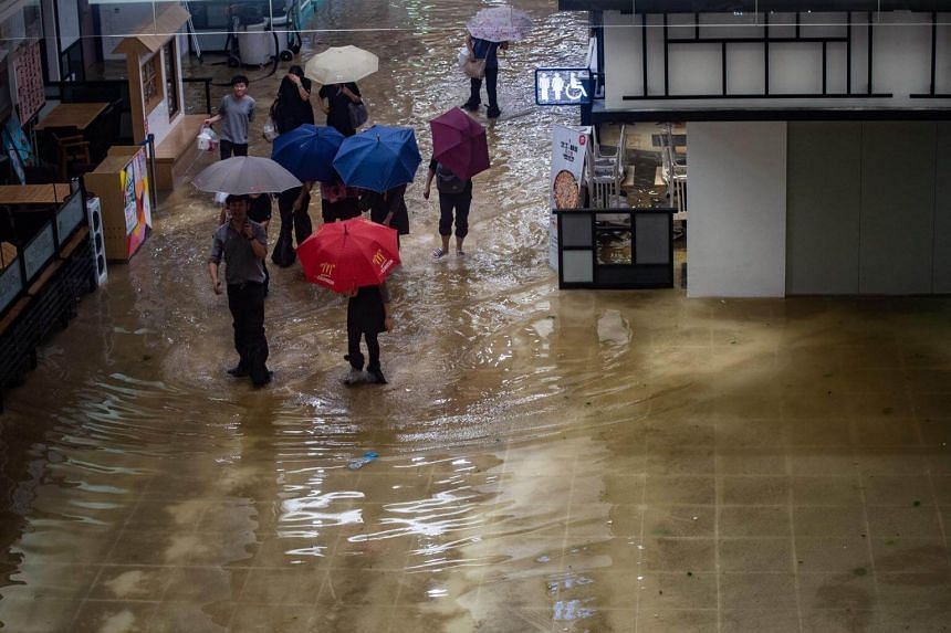 People walk through a flooded shopping mall in Heng Fa Chuen district during Super Typhoon Mangkhut in Hong Kong, on Sept 16, 2018.