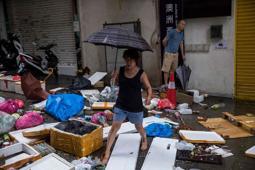 A woman steps through rubbish and debris left by Typhoon Mangkhut in Macau, on Sept 16, 2018.