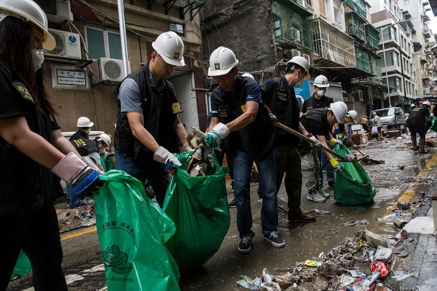 Police clear rubbish and debris from a street after Typhoon Mangkhut hit Macau, on Sept 17, 2018.