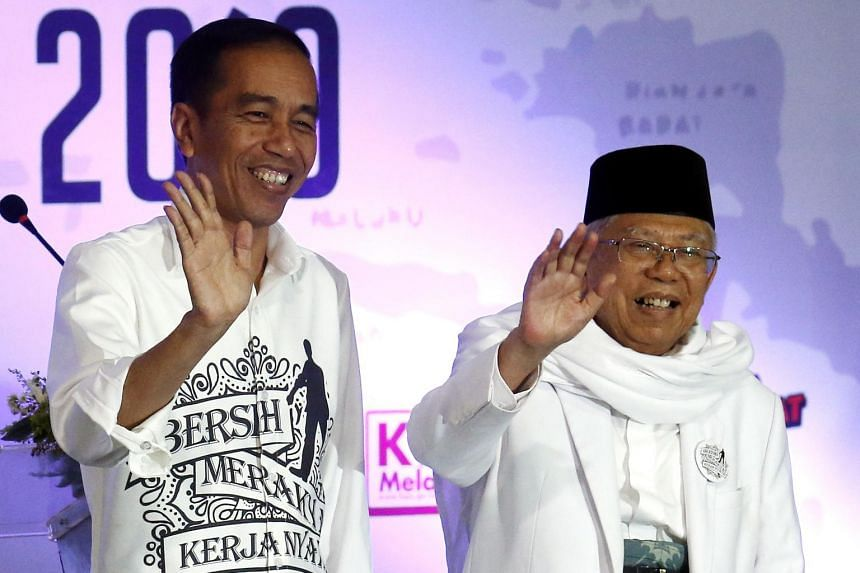 Indonesian incumbent Presidential candidate Joko Widodo (left) and his running mate Ma'ruf Amin wave after registering for the 2019 presidential election, on Aug 10, 2018.
