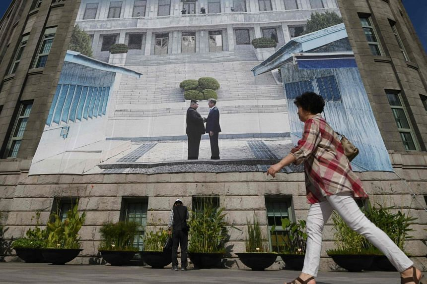 A woman walks past a giant banner showing a picture of the summit handshake between South Korean President Moon Jae-in and North Korean leader Kim Jong Un, at Seoul City Hall, on Sept 13, 2018.