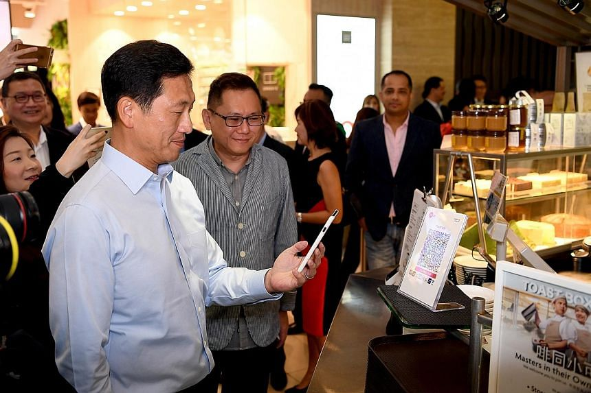 Mr Ong Ye Kung, Education Minister and MAS board member, making payment via the SGQR code at a Toast Box outlet yesterday. With him is Mr Vincent Lim, regional general manager for Toast Box. For consumers, SGQR means more chances that the cashless sc