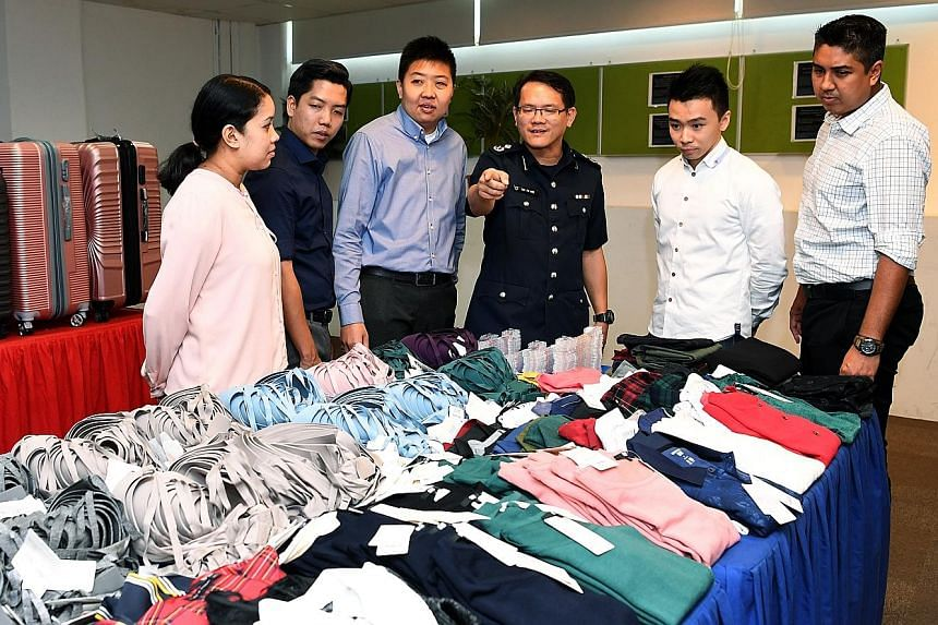Assistant Commissioner of Police Tan Tin Wee (fourth from left) and officers who helped bust the syndicate with the stolen goods. The police described it as the largest shop theft case, in terms of value and volume, that they have come across in rece