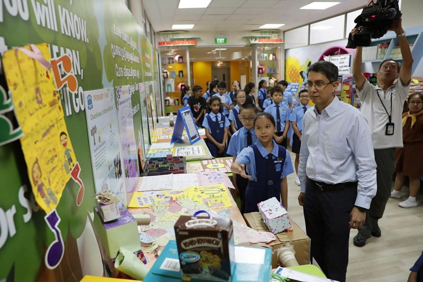 Associate Professor Muhammad Faishal Ibrahim views projects done by Chongzheng Primary School students during a visit to learn more about the school's Values in Action(VIA) programme, on Sept 18, 2018.
