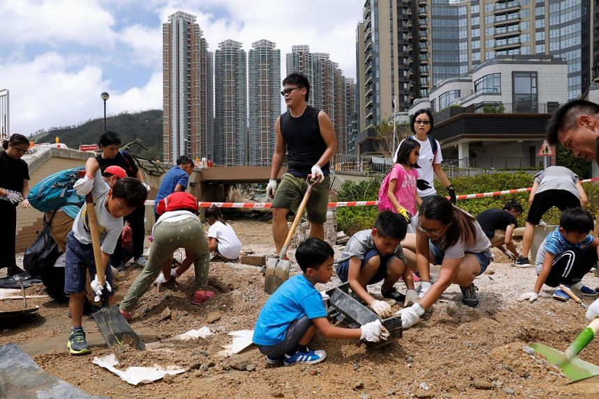 Volunteers clear a damaged path on Sept 18, 2018, after Super Typhoon Mangkhut hit Hong Kong.