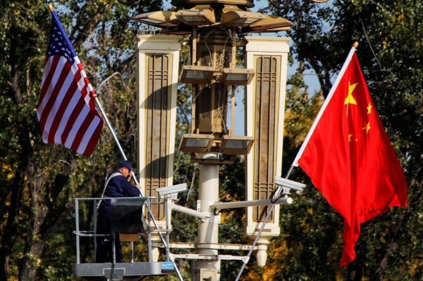A worker places US and China flags near the Forbidden City ahead of a visit by US President Donald Trump to Beijing, China, on Nov 8, 2017.