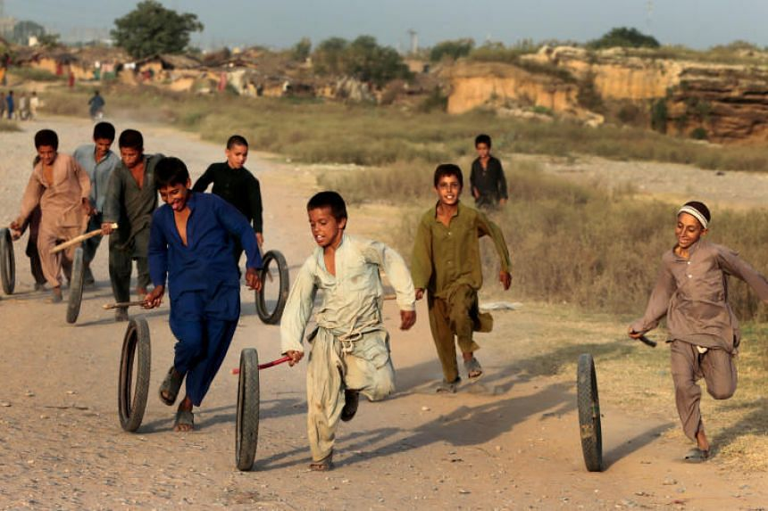 Afghan refugee children play with tyres in Islamabad, Pakistan, on Oct 6, 2017.