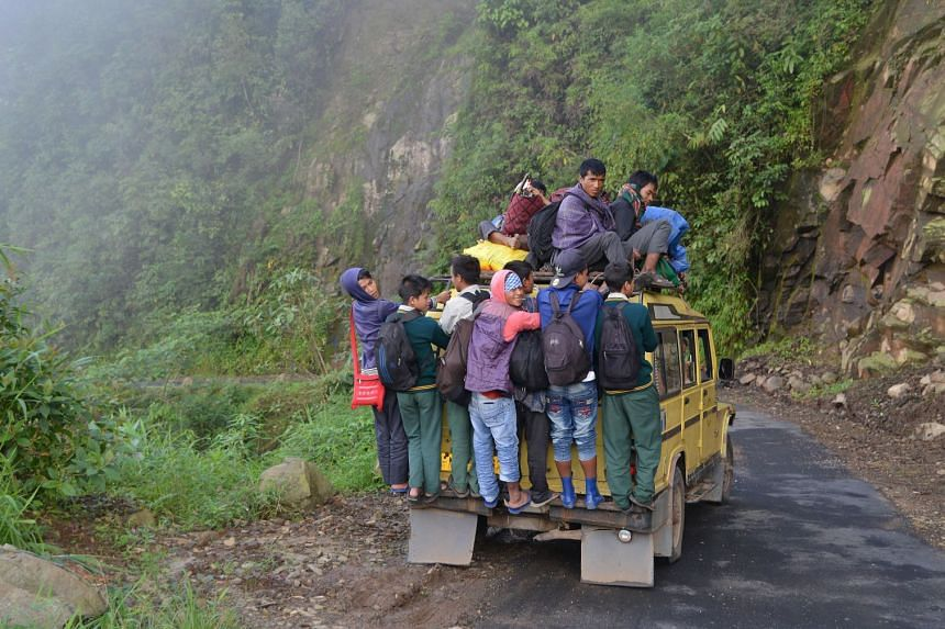 Indian villagers and school children on an overcrowded vehicle as they travel to Kongthong village.
