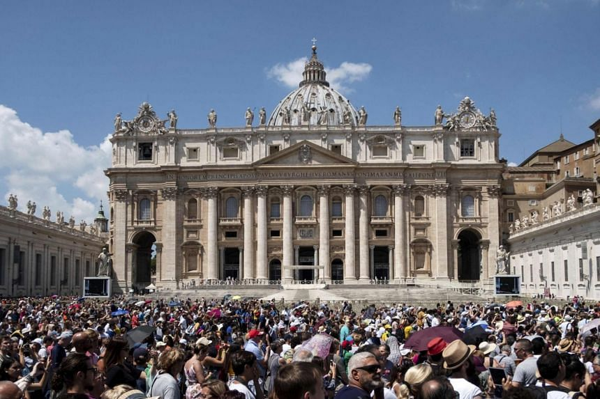 People outside the Apostolic Palace overlooking Saint Peter's Square next to Saint Peter's Basilica, on July 22, 2018, at the Vatican.