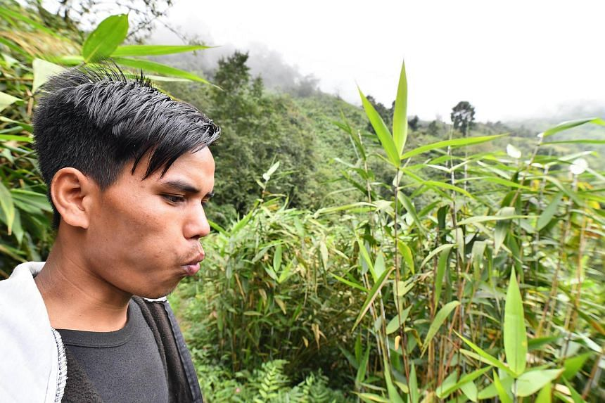 An Indian villager whistling as he calls to a friend in a field in Kongthong village.